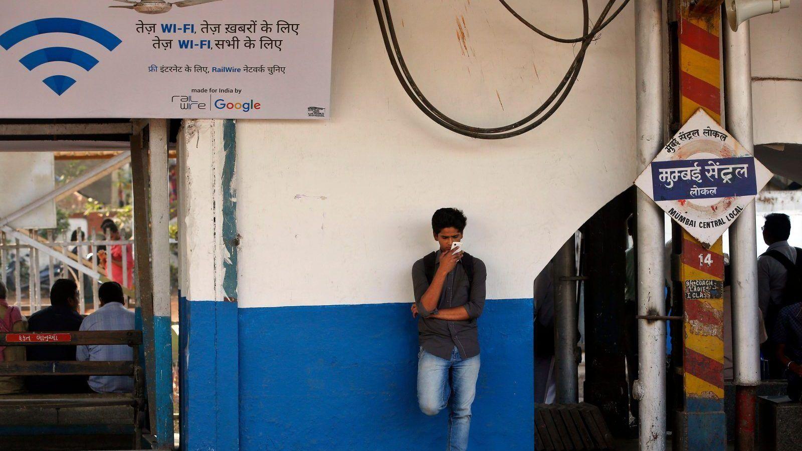 Un voyageur indien utilise un service Wi-Fi gratuit pour naviguer sur Internet à la gare centrale de Mumbai, en Inde, le vendredi 22 janvier 2016. Google Inc. a commencé à offrir une connexion Wi-Fi gratuite aux passagers des trains de Mumbai dans l'espoir de renforcer son rôle dans Marché indien.  Une affiche sur la gauche dit «WiFi rapide, pour des nouvelles rapides, WiFi rapide, pour tout le monde».  (AP Photo / Rajanish Kakade)