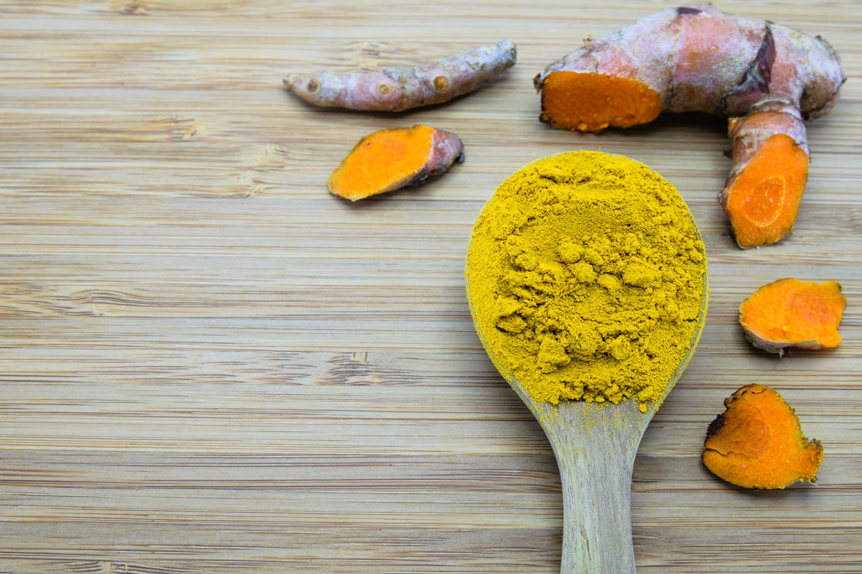 turmeric powder in wood spoon and turmeric root on wood background