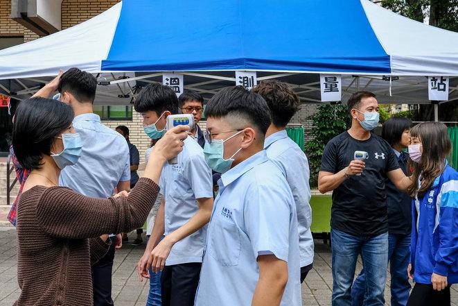 Prise de température et distribution de masques dans un lycée de Banqiao à New Taipei. © Yen-Ting Lin